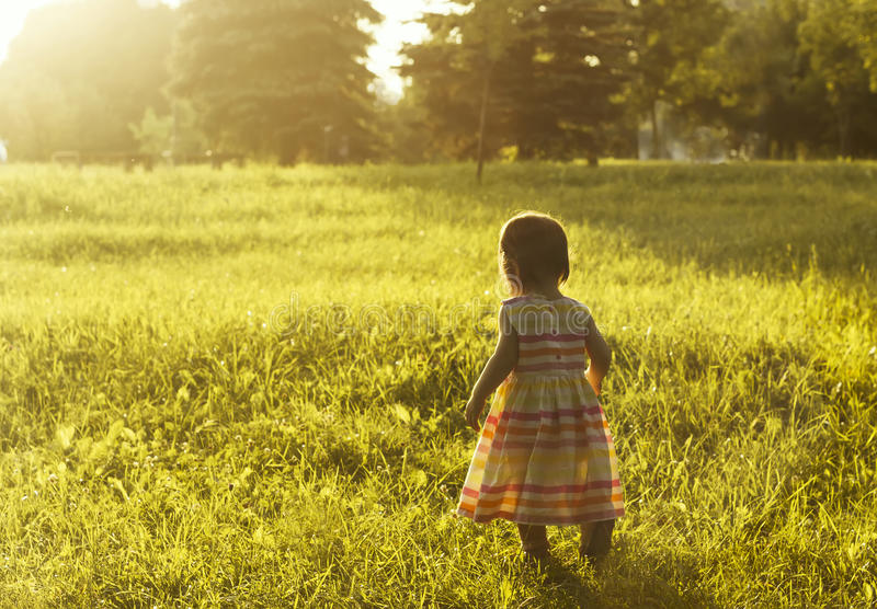 Little girl running on meadow with sunset stock photo