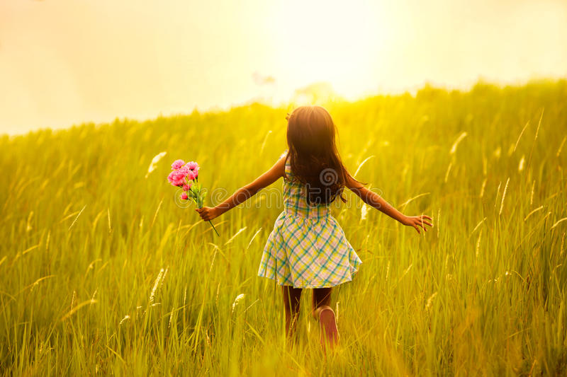 Little girl running on meadow with sunset. Outdoor portrait royalty free stock images
