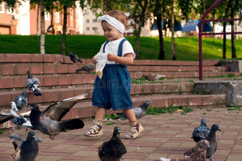 Little girl running near doves, chasing pigeons, happy child with smiling face. Kid is feeding pigeons in city park royalty free stock photo
