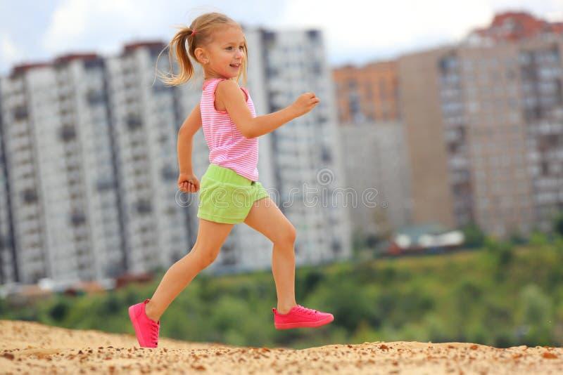 Little girl running in sand stock photography