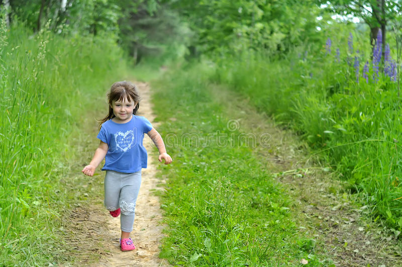 Little girl running in sunny blooming forest. Kids play outdoors. Summer fun for family with children. royalty free stock image