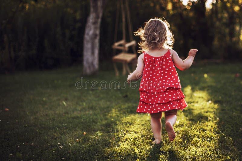 Little girl running at sunset stock images
