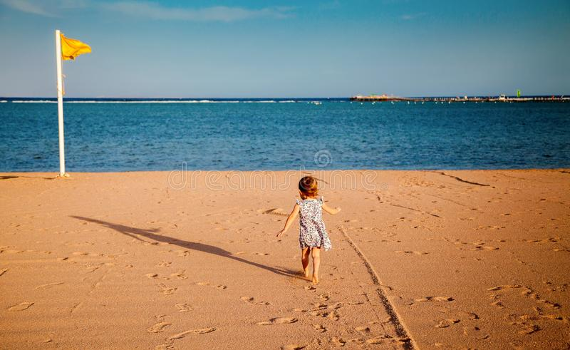 Girl running towards the sea royalty free stock photo