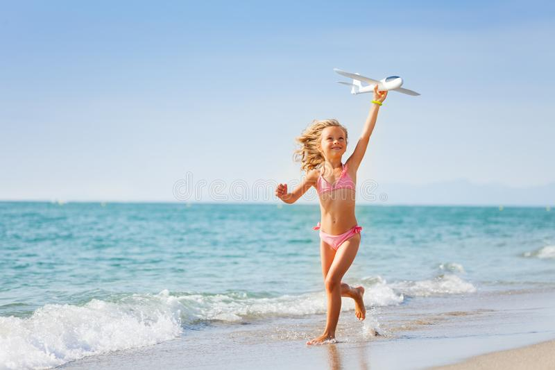 Little girl running with toy plane on the beach stock photography