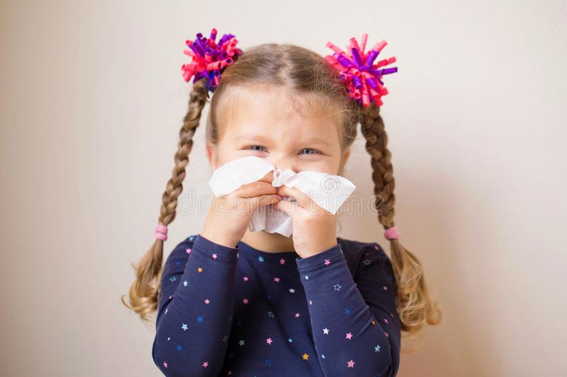 The little girl with runny nose blows into handkerchief. The little girl has a runny nose and blows her nose into a paper handkerchief. Children`s cold stock photos