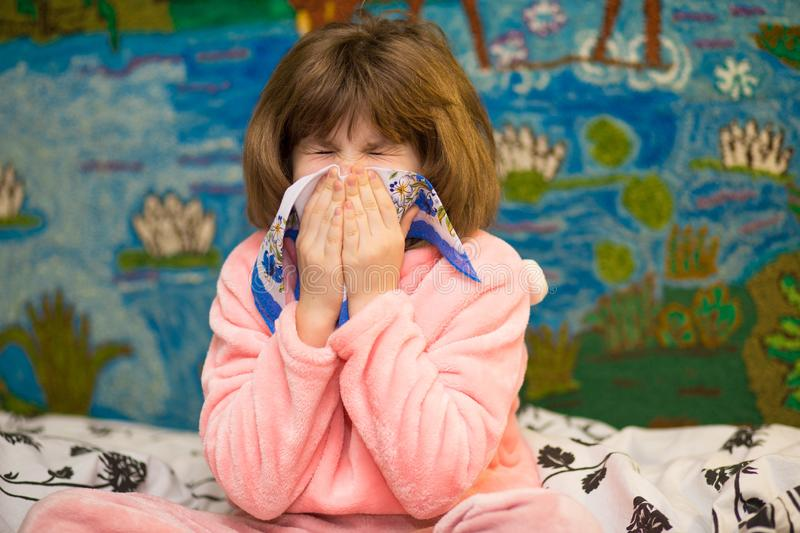 Little girl with runny nose wipes her nose. Health concept stock photography