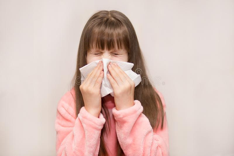 Little girl with runny nose wipes her nose. Health concept stock photo