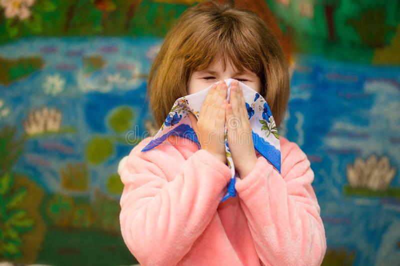 Little girl with runny nose wipes her nose. Health concept royalty free stock image