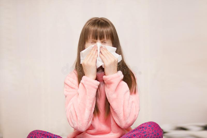 Little girl with runny nose wipes her nose. Health concept royalty free stock photo