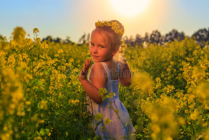 A little girl runs through a field of. A four-year-old girl runs through a field of stock images