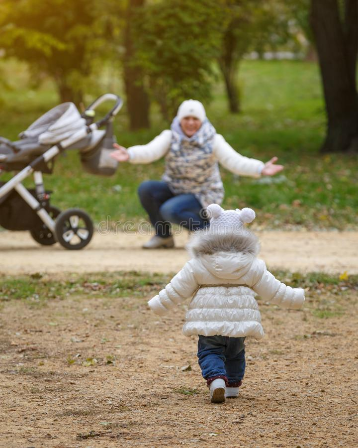 Little girl runs to her mom with a baby stroller in parkland. Mom and daughter reach out to each other stock image