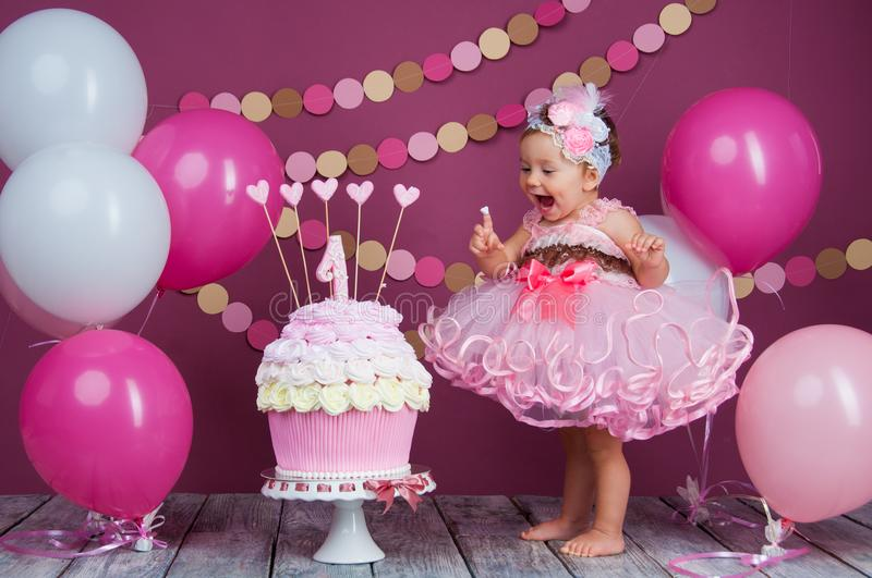 The little girl`s birthday girl was smeared into a cake. The first cake. The use of the first cake. Smash cake. stock photos