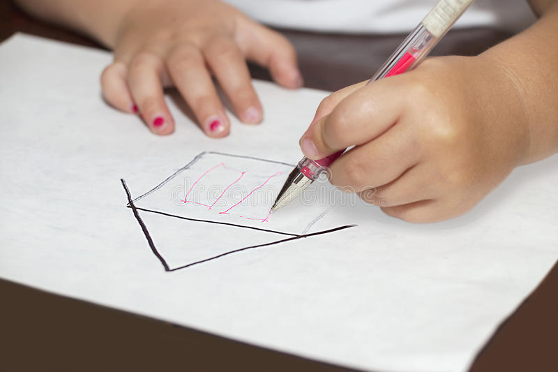 Little girl's hands with ballpen drawing a house. On a white paper royalty free stock photo