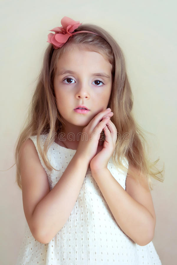 Little girl's portrait. Tender serious child, fashion model. stock photo
