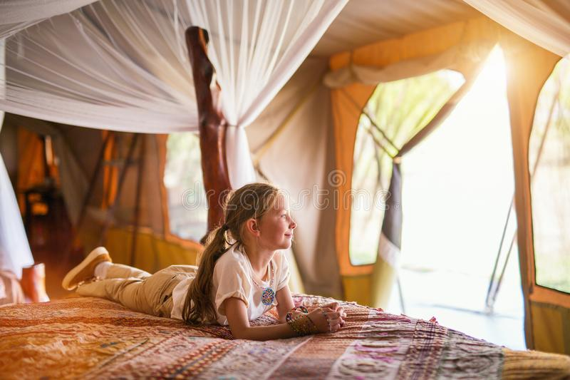 Little girl on safari. Little girl in safari tent enjoying luxury vacation in Africa royalty free stock images