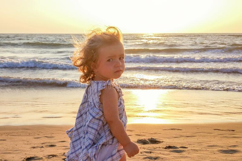 A little girl on a sandy beach against the background of the setting sun and sea waves looks at the camera, the average plan, sun. Glare and color illumination stock images