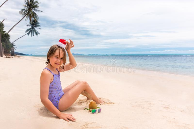 Little girl in Santa Claus red hat plays with coconut on sand on a tropical beach. Holiday tropic summer concept royalty free stock images