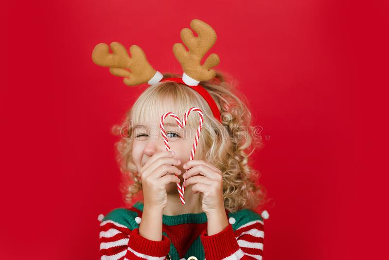 Little girl in Santa elf helper costume on bright red vivid color background stock photos