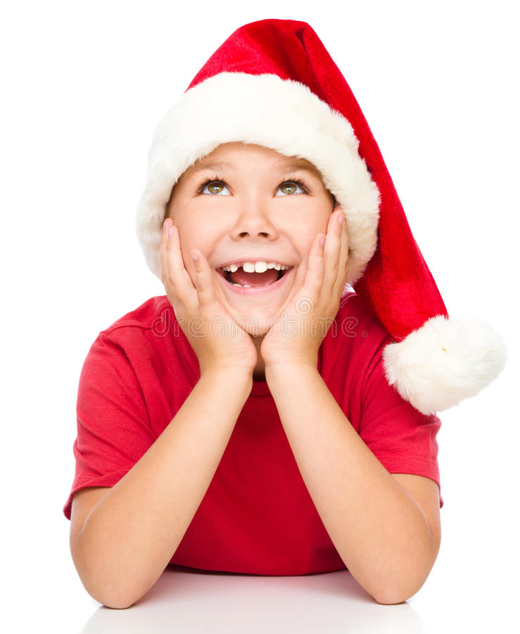 Little girl in santa hat is daydreaming. Supporting her head with hands, isolated over white royalty free stock photos