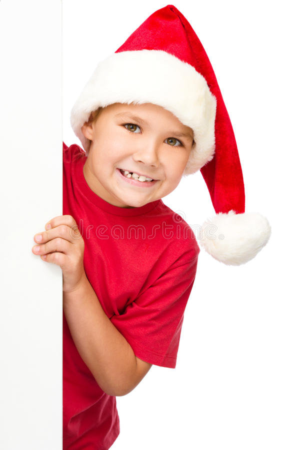 Little girl in santa hat is holding blank board. Isolated over white royalty free stock photos