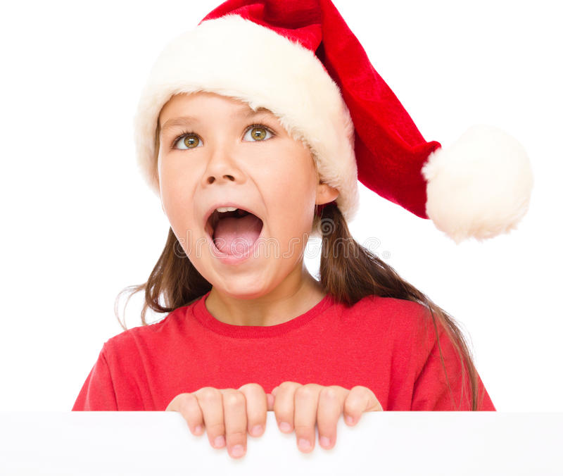 Little girl in santa hat is holding blank board. And screaming, isolated over white stock image