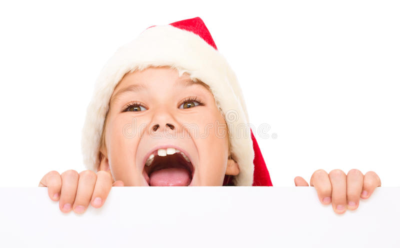 Little girl in santa hat is holding blank board. And screaming, isolated over white royalty free stock photography