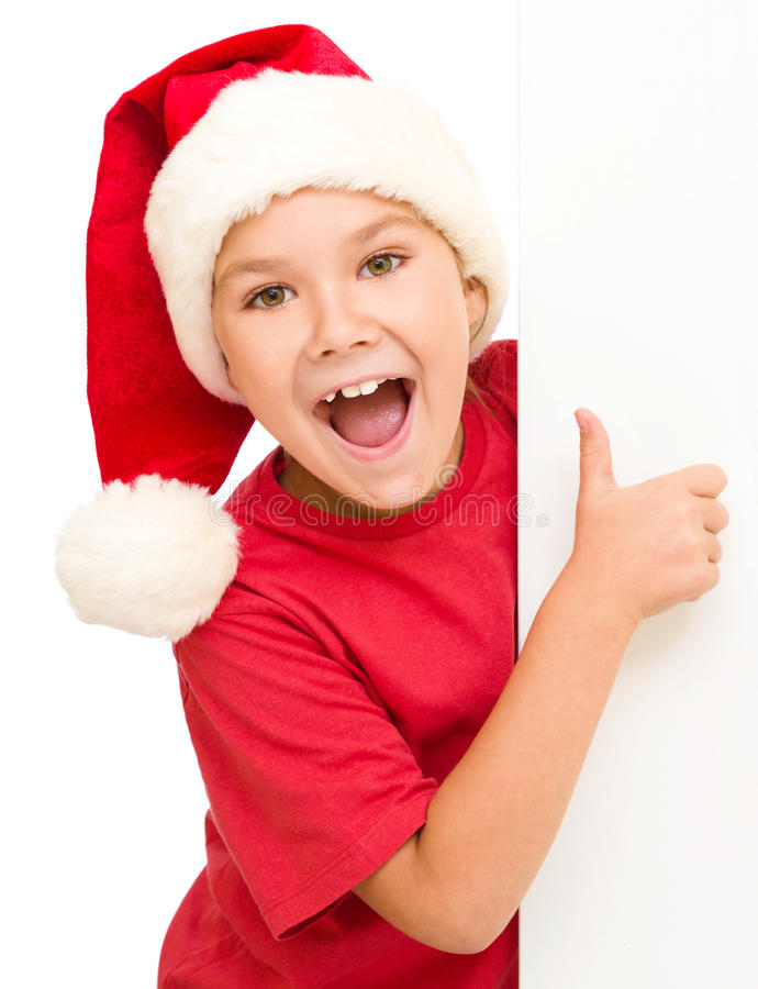 Little girl in santa hat is holding blank board. And showing thumb up sign, isolated over white royalty free stock photos