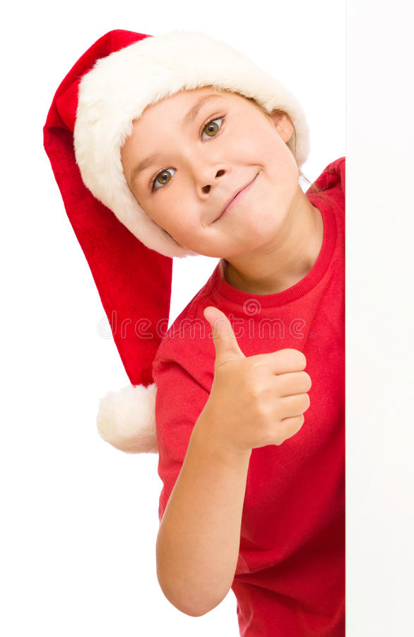 Little girl in santa hat is holding blank board. And showing thumb up sign, isolated over white royalty free stock photo