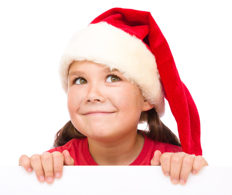 Little girl in santa hat is holding blank board. And smiling, isolated over white stock photos