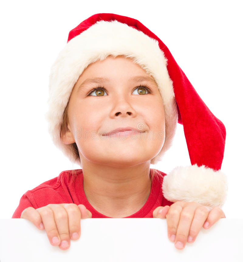 Little girl in santa hat is holding blank board. And smiling, isolated over white stock photo