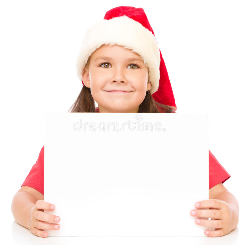 Little girl in santa hat is holding blank board. And smiling, isolated over white royalty free stock photography