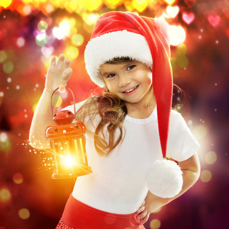 Little girl in Santa hat holding red Christmas stock photo