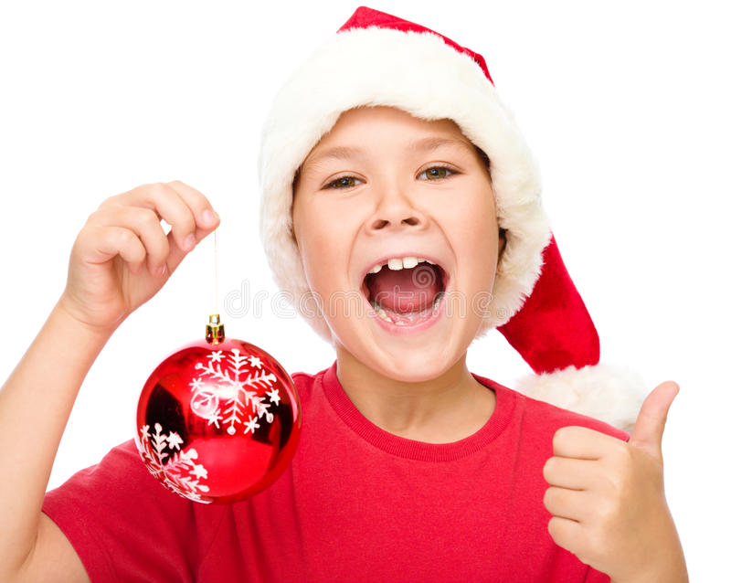 Little girl in santa hat is showing thumb up sign. Little girl in santa hat is holding a christmas decoration and showing thumb up sign, isolated over white royalty free stock photo