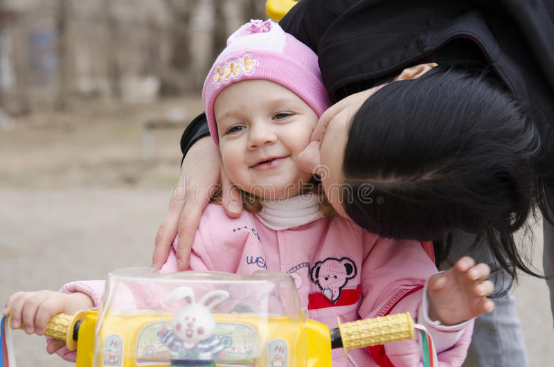 A little girl sitting on a bike kissed my mother stock photography