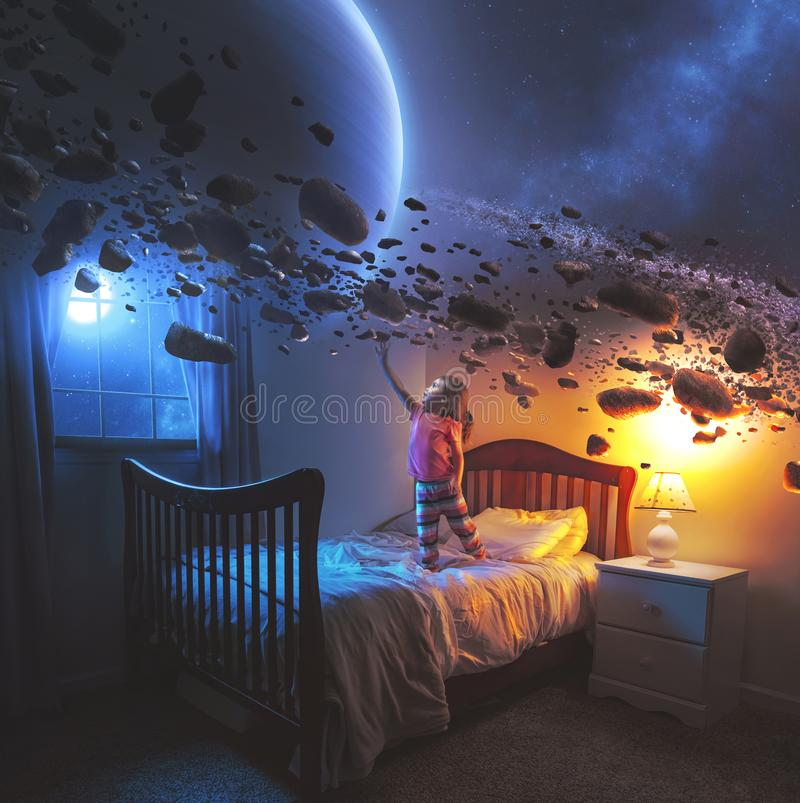 Little girl and Saturn`s rings. A little girl uses her imagination in her bedroom to see the rings of Saturn stock photo