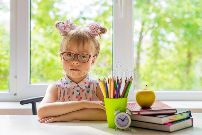 Little girl with school supplies is sitting at the table. royalty free stock photos