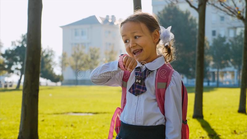 A little girl in school uniform is walking and talking on smart watches. stock image