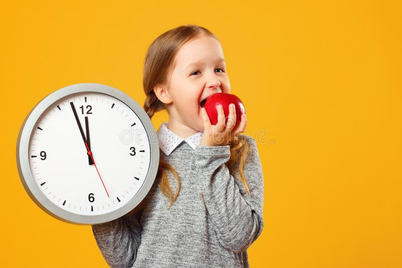 Little girl schoolgirl holds a big clock and bites a red apple on a yellow background. Break and lunch royalty free stock photography