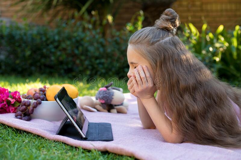 Little girl, schoolgirl looks in a laptop in the garden stock image