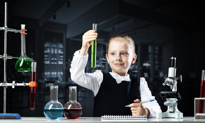 Little girl scientist examining test tube stock photo