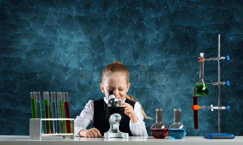 Little girl scientist looking through microscope stock image