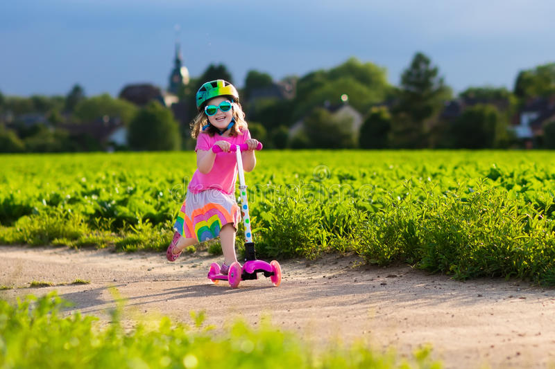 Little girl on a scooter. Little child learning to ride a scooter in a city park on sunny summer day. Cute preschooler girl in safety helmet riding a roller royalty free stock photo