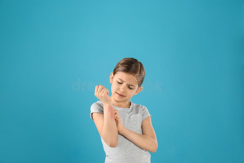 Little girl scratching forearm. Allergy symptoms. Little girl scratching forearm on color background. Allergy symptoms royalty free stock images