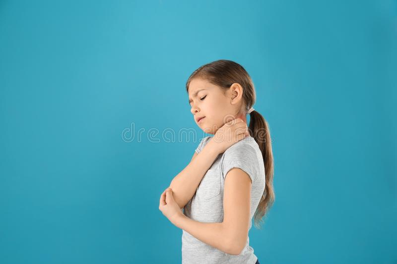 Little girl scratching neck on color background. Allergy symptoms. Little girl scratching neck on color background, space for text. Allergy symptoms royalty free stock images