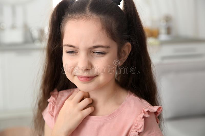 Little girl scratching neck at home. Annoying itch royalty free stock photo