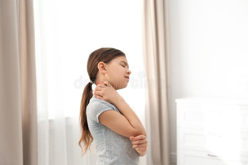 Little girl scratching neck. Allergy symptoms. Little girl scratching neck indoors. Allergy symptoms royalty free stock image