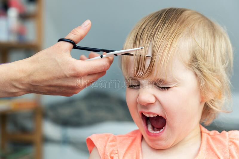Little girl screaming while mother doing a haircut at home royalty free stock photography