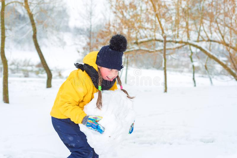 Little girl sculpts snowman. the kid is carrying a lump of snow. Little girl sculpts snowman. the kid in the yellow jacket is carrying lump of snow royalty free stock photography