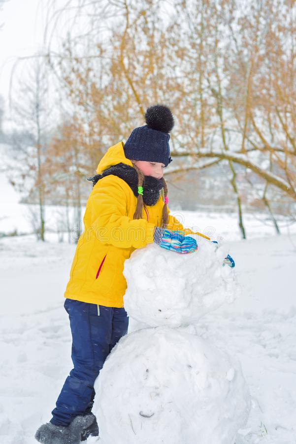 Little girl sculpts snowman. the kid is carrying a lump of snow. Little girl sculpts snowman. the kid in the yellow jacket is carrying lump of snow royalty free stock images