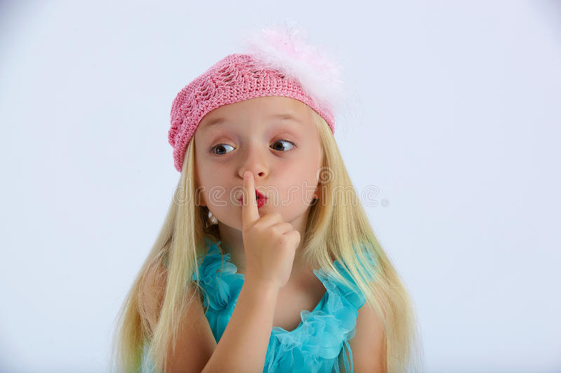 Little girl with a secret. Little girl wearing a pink crochet hat over her long blond hair holds her finger to her lips to keep in her secret royalty free stock photos